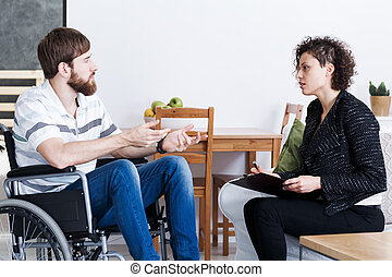 Man in wheelchair talking with psychotherapist