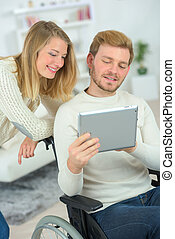 Man in wheelchair using a tablet computer with his girlfriend