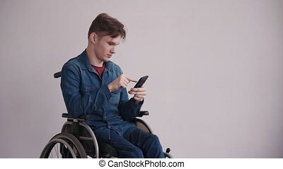 Man in wheelchair using modern cellular at home - Young and...