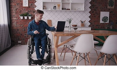 Man in wheelchair using modern computer at home - Adult...