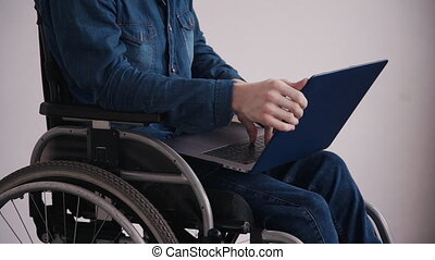 Man in wheelchair using modern personal computer at home -...