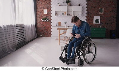 Man in wheelchair using smart cellular at home - Adult...