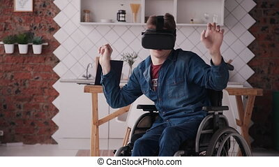 Man in wheelchair using vr glasses and heaving fun at home -...