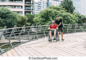 man in wheelchair walking at park with a friend