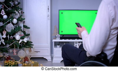 Man in wheelchair with remote control watching tv green screen on Christmas. Dolly shot 4k