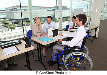 Man in wheelchair working in an office