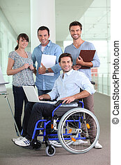 Man in wheelchair working with colleagues