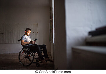 Man in wheelchair working with tablet.