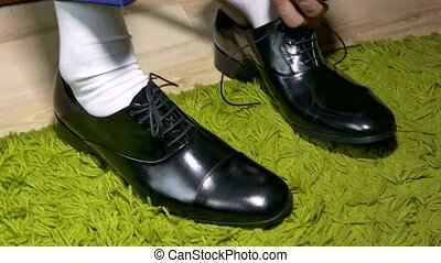 man in white dress socks to tie shoelaces shoes - man in...