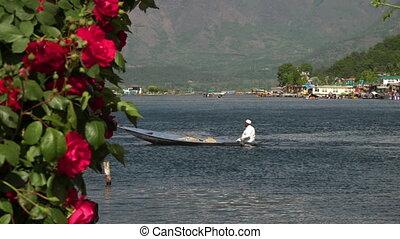 Man in white paddling a canoe across Dal lake - Wide shot of...