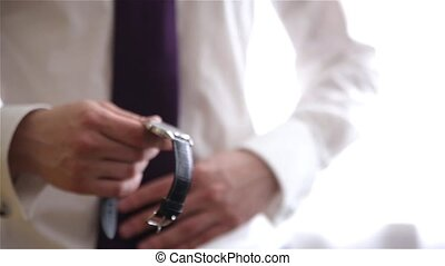 Man in white shirt and tie wearing the stylish watch - A man...