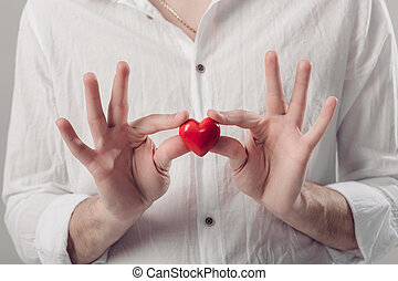 man in white shirt holds in hands red heart on gray background.