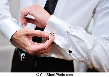 man in white shirt near window dress cufflinks.