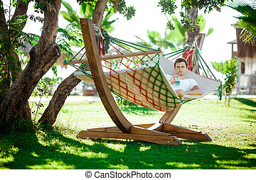 man in white shirt relaxing in hammock