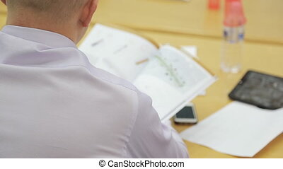 Man in white shirt sitting at table studying construction plan at meeting.