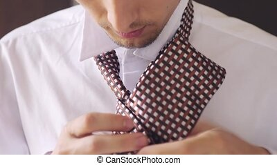 Man in white shirt tying a tie. Close up. - Man in white...