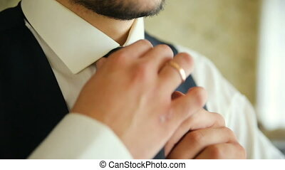 Man in white shirt tying a tie near the window. Close-up