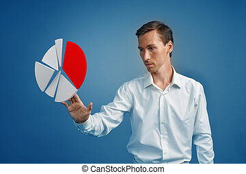 Man in white shirt working with pie chart on blue background.
