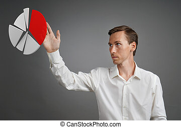 Man in white shirt working with pie chart on grey background.