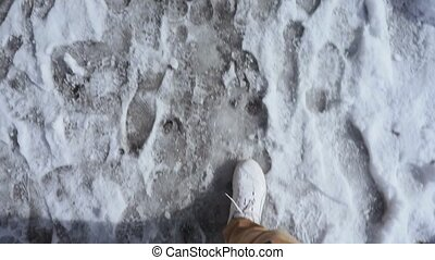 man in white sneakers walks on a wet snow muddy road in ...