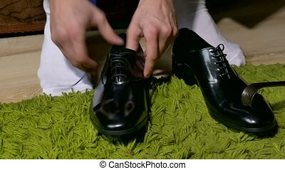 man in white socks dress shoes to tie shoelaces - man in...