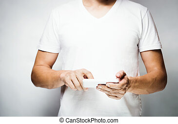 Man in white t-shirt using mobile smart phone,white wall on...
