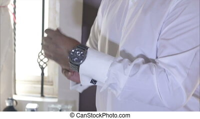 man in white wedding shirt clasps watches on hand