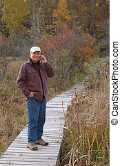 handsome man in wilderness on cell phone 228 smiling