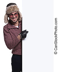 man in winter clothes and fur hat is pointing to a blank board