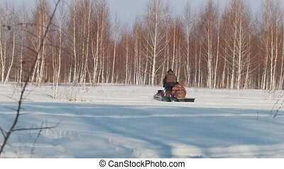 Man in winter clothes fast riding and carrying passenger in...