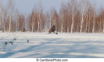 Man in winter clothes fast riding, maneuvering and carrying...
