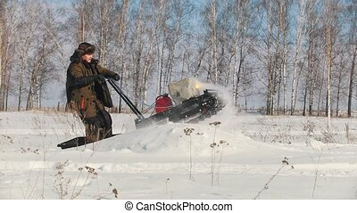 Man in winter clothes overcoming high snow on a mini...