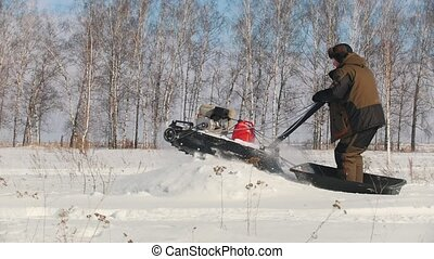 Man in winter clothes overcoming high snow on a mini snowmobile and jumping through the drift