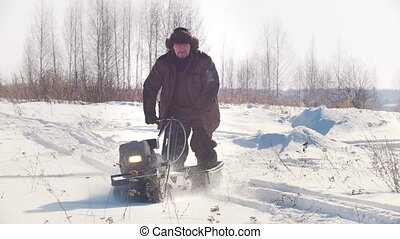 Man in winter clothes riding on crawler mini snowmobile in the winter through the snow