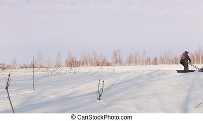 Man in winter clothes walking and riding on mini snowmobile on deep snowdrifts in the field