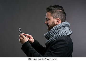 Man in winter clothes with smartphone texting, studio shot