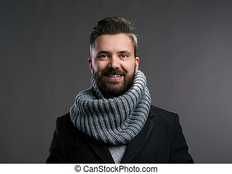 Man in winter coat and kintted scarf. Studio shot