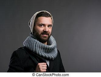 Man in winter coat, scarf and beanie. Studio shot