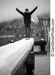 Man in winter jacket standing at the end of a snowy pier