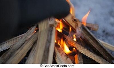 Man in winter watching fire putting new stick to it. Fold a...