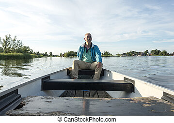 man in wooden boat on the lake