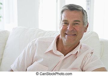 man, in, woonkamer, het glimlachen