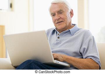 man, in, woonkamer, met, draagbare computer, het glimlachen