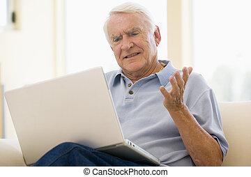 man, in, woonkamer, met, draagbare computer