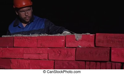 Man in working equipment builds a wall of brick. Stock....