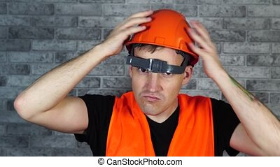 Man in working uniform turning orange protective hardhat.