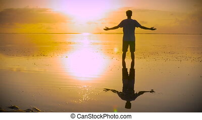 Man in worship pose on beach reaching out towards the sun Thankful