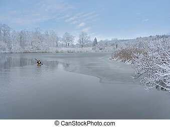 Man in yellow kayak in partly frozen river with blue sky