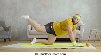 Fat man in yellow sportswear is doing legs lifting exercises standing on knees on mat training at home in living room, side view. Sport, workout, concept. Joke, mem, fitness humor.
