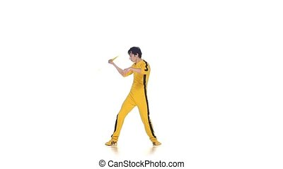 Man in yellow suit training karate and expertly twirling...